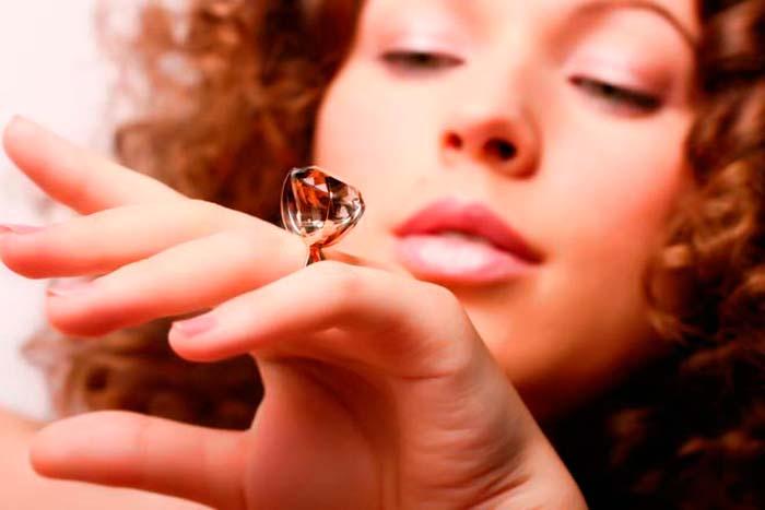 смотрит на кольцо с камнем